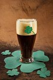 Dark Irish beer for St Patick's Day. On napkins stylized under clover leaf Stock Photos