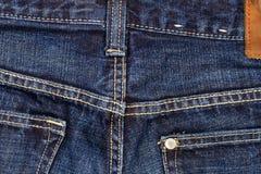 Dark jeans texture. Worn blue denim jeans texture with stitch Stock Photo