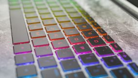 Dark keyboard gaming laptop with rgb backlight. Dark keyboard of a gaming laptop with gradient rgb back-light close up angular view, defocused stock images