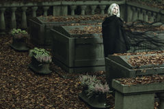 Dark lady posing in a graveyard. Dark lady posing with sad expression in a graveyard . Halloween and horror stock photo