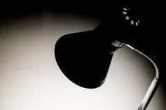 Dark light. Back lamp lighting to the desk in the dark Stock Photo