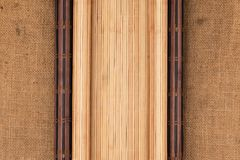 Dark and light bamboo mat in the form of a scroll lie on the sacking. View from above royalty free stock photography