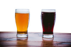 Dark and light beer on the bar on a white background Stock Images