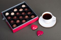 Red and silver box of dark and light chocolate candy. Dark and light chocolate candy in a red and silver box next to coffee in a white cup and saucer trimmed royalty free stock images