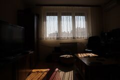 Free Dark Living Room With Windows Lighten By Sun, Back Lit Interior Shot Of A Dimly-lit Back Room. Sunbeams Coming In Dark Room Threw Royalty Free Stock Photo - 185535565