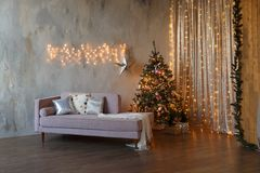 Dark loft living room decorated for Christmas with tree and lights royalty free stock image