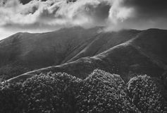 Dark low clouds above the mountains. Black and white Royalty Free Stock Image