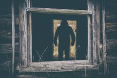 Dark male silhouette in the doorway of abandoned house. Dark male silhouette standing in the doorway of abandoned house. View through the broken window Royalty Free Stock Images