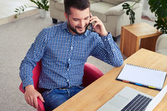 Dark male talking on telephone while working. High-angled shot of dark male talking on telephone while working Stock Images