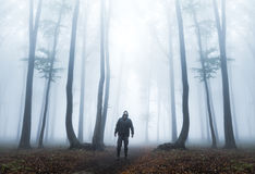 Dark man looks up in misty forest Stock Photo