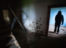 Dark man in old house. A dark man silhouette standing in an old abandoned house royalty free stock photo