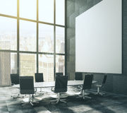 Dark meeting room with blank picture frame and table. Mock up Stock Image