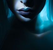 Dark mesmerising lips closeup. Beauty lips with atmospheric light effect comming out of the dark, blue lips with grey closeup Royalty Free Stock Photo