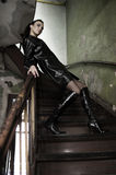 The dark model. Fashion shot of a brunette model with black leather coat and boots posing in old stairs Stock Photography