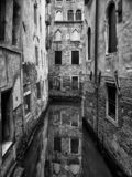 Dark monochrome image of a quiet narrow canal in venice surrounded by picturesque ancient buildings reflected in the water stock image