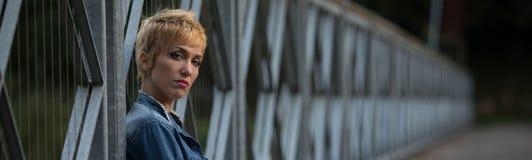 Dark moody panorama of a serious blond woman Stock Photos