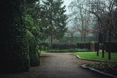 Dark moody park pathway landscape on a wet rainy day. Color graded Royalty Free Stock Images
