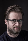 Dark moody portrait of caucasian bearded man in glasses. Portrait face of forty years old caucasian handsome bearded man in glasses - close up. Black background Stock Images