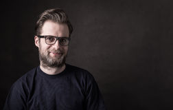 Dark moody portrait of happy caucasian man in glasses. Portrait of happy smiling forty years old caucasian man in casual t-shirt and glasses. Black background royalty free stock photos