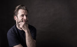 Dark moody portrait of happy caucasian man. Portrait of happy smiling forty years old caucasian man in casual t-shirt. Black background, dark moody concept stock images