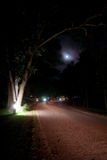 Dark moonlit road. A road at night lit by some lights and the moon stock photography