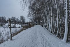 Dark morning with snow winter path near pond in Telc town stock photography