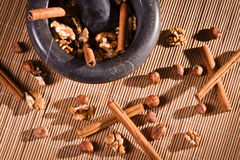 Dark mortar and all sorts of nuts. On bamboo mat royalty free stock photography