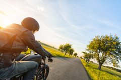 Dark motorbiker riding high power motorbike in sunset Royalty Free Stock Photos