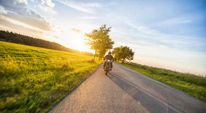 Dark motorbiker riding high power motorbike in sunset Stock Photos