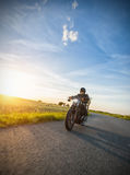 Dark motorbiker riding high power motorbike in sunset Royalty Free Stock Image