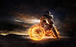 Dark motorbiker staying on burning motorcycle in sunset light Royalty Free Stock Photos