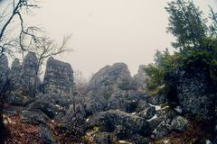 Dark mountain landscape with big mysterious rocks covered by fog Stock Photos