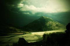 Dark mountain and river, Albania. Dark mountain and river with small sandy storm in the Albania royalty free stock photo