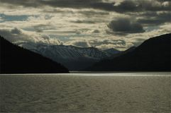 Dark mountains across a lake. With storm clouds and sun rays on the water Stock Photography
