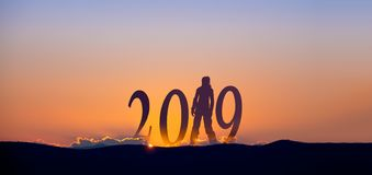 2019 On dark mountains with silhouette of a woman and sunrise as background. royalty free stock photo