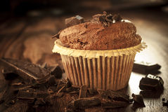Dark muffin with chocolate. On a dark wooden table Royalty Free Stock Images