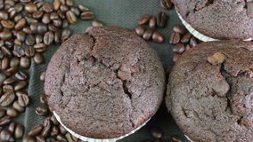 Dark muffins and coffee beans on black background. Dark muffins and coffee beans on black background stock video footage