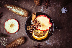 Dark mulled wine cup with fruits and winter spices, on wooden background Royalty Free Stock Photography