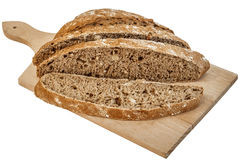 Dark Multigrain Bread Loaf Sliced on Cutting Board Isolated on White Background Royalty Free Stock Photo