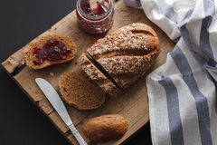 Dark multigrain bread whole grain and jam fresh baked on rustic Stock Image
