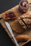 Dark multigrain bread whole grain and jam fresh baked on rustic Royalty Free Stock Photo