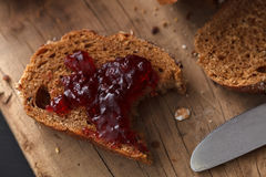Dark multigrain bread whole grain and jam fresh baked on rustic Royalty Free Stock Photos