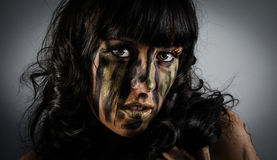 Dark and mysterious with camoflauge paint on face. Dark and mysterious a pretty girl stands in shadow with camoflauge paint on her face Royalty Free Stock Photo