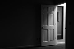 Dark and mysterious room. View from a dark and mysterious room with door open and light coming in from outside the room Royalty Free Stock Image