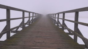 Dark and mystical early morning fog on empty wooden bridge stock video footage
