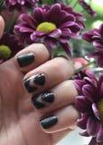 Dark nails. Art flowers manicure magenta black polish painted fingers royalty free stock photo