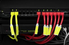 Dark Network. Desaturated ethernet switch and router with red and yellow network cables tagged and ready for your text royalty free stock photo