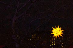 Star Light. Edinburgh`s Christmas, Princes Street Gardens, Edinb. Dark night, city scene. A many sided yellow glowing star light in a tree with city apartment Royalty Free Stock Photography
