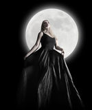 Dark Night Moon Girl with Black Dress. A woman is wearing a long black dress moving in the dark night against a full moon for a fashion or mystery concept Stock Images