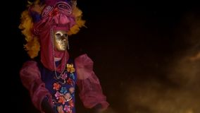 Dark night a mysterious girl in a mask and colorful costume dancing in a burning fire.  stock video footage